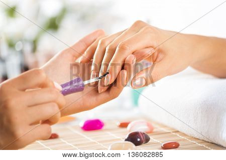 Woman in salon receiving manicure by nail beautician