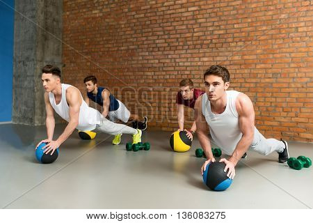 Strong young men are doing push-ups in group. They are leaning hands on fitness ball near dumbbells. Athletes are looking forward with aspiration