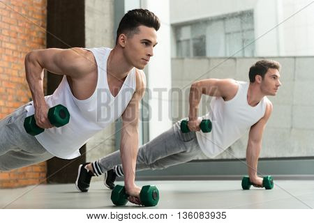 Strong two men training body in gym. They are doing push-ups while holding dumbbells. Sportsmen are looking forward with aspiration