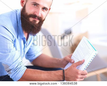 Young male office worker sitting on chair in office .