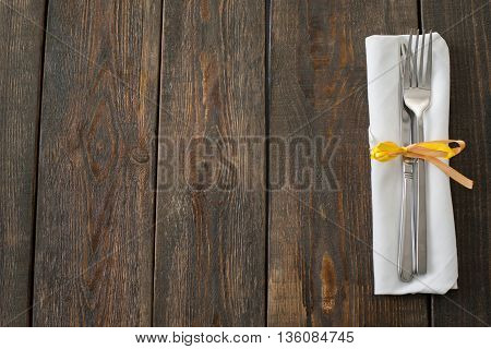 Fork and knife on dark wooden background copyspace. Top view on white napkin with knife and fork on right side of picture on wooden background. Free space for restaurant advertisement, commercials