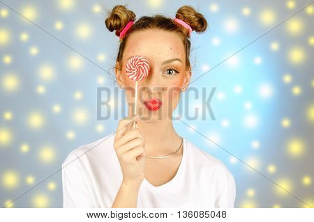 beautiful happy girl with freckles holding and eating sweets candy lollipop with facial expression