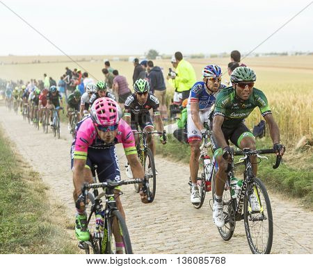 Quievy, France - July 07 2015: The French cyclist Yohann Gene of Europcar Team riding in the peloton on a cobblestone road during the stage 4 of Le Tour de France 2015 in Quievy France on 07 July2015.