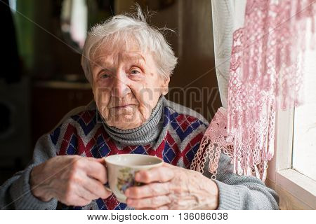 Elderly woman drinking tea sitting in the kitchen.