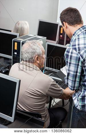 Tutor Assisting Senior Man In Using Computer At Classroom