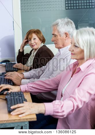 Confident Senior Woman Sitting With Classmates At Computer Desk