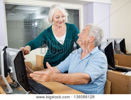 Woman Assisting Classmate In Using Computer At Classroom