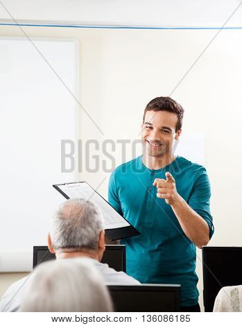 Happy Tutor Taking Lecture In Computer Class