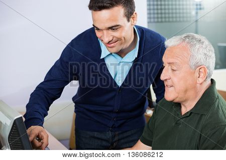 Smiling Teacher Assisting Senior Man In Using Computer