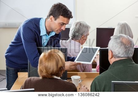 Teacher Showing Digital Tablet To Senior Students In Computer Cl