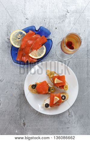 Tasty various italian sandwiches with seafood against rustic wooden background. Crostini with cheese red fish and olives on white plate glass of wine top view