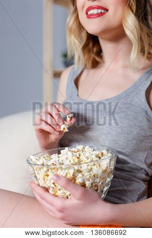 Joyful young woman is eating popcorn and smiling. She is sitting on sofa at home and relaxing