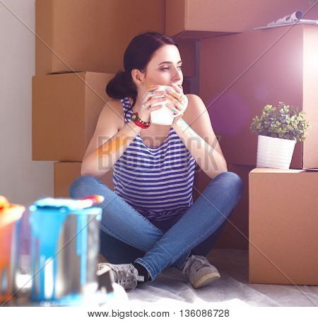 Woman in a new home with cardboard boxes.