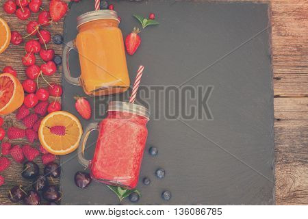Fresh smoothy citrus and berry drinks with igredients and copy space, retro toned