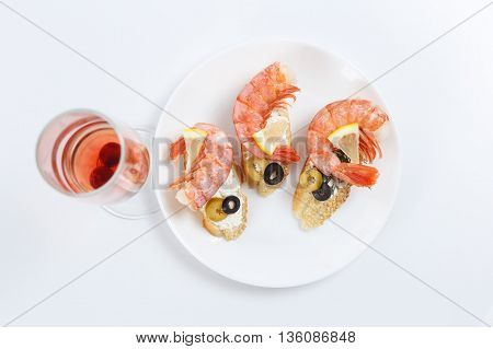 Tasty various italian sandwiches with seafood against white background. Crostini with cheese shrimps and olives on white plate glass of wine horizontal top view