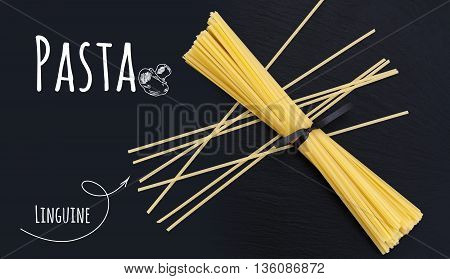 Uncooked Italian pasta Linguine on black slate stone background with white lettering top view