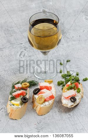 Tasty various italian sandwiches with seafood against rustic wooden background. Crostini with cheese crab sticks and olives herbs and wine close up with selective focus