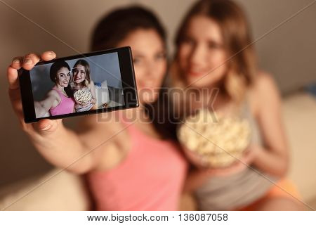 Joyful two girls are making selfie and smiling. Woman is holding a mobile phone. Her friend is carrying a bowl of popcorn. They are sitting on sofa