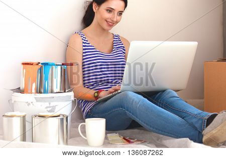 Young woman portrait while painting new apartment  , sitting with laptop.