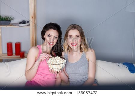 Cheerful friends are watching tv at home together. They are sitting on sofa and eating popcorn. Girls are smiling