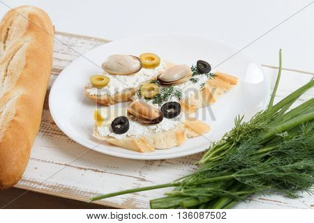 Tasty various italian sandwiches with seafood against rustic wooden background. Crostini with cheese mussels and olives on white plate bread and herbs horizontal view with selective focus