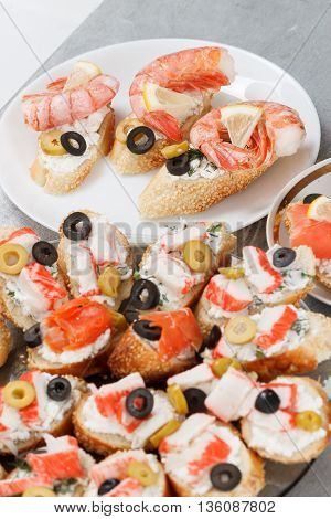 Tasty various italian sandwiches with seafood against rustic wooden background. Crostini with cheese shrimps mussels red fish crab sticks lemon sliced olives on different plates close up with selective focus