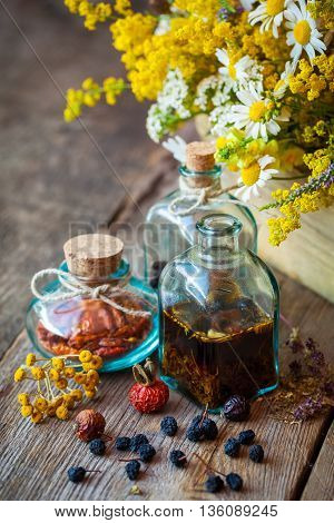 Bottles Of Tincture And Dry Healthy Herbs, Bunch Of Healing Herbs In Wooden Box On Table. Herbal Med