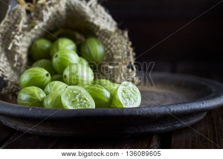 Gooseberries on dark background coming out of burlap bag. Copy space