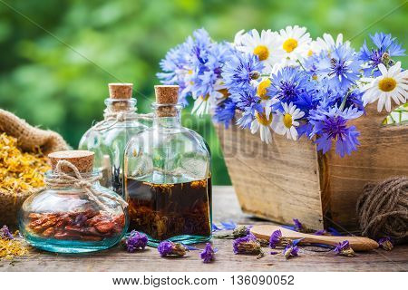 Bottles Of Tincture And Dry Healthy Herbs, Bunch Of Healing Flowers In Wooden Box On Table. Herbal M