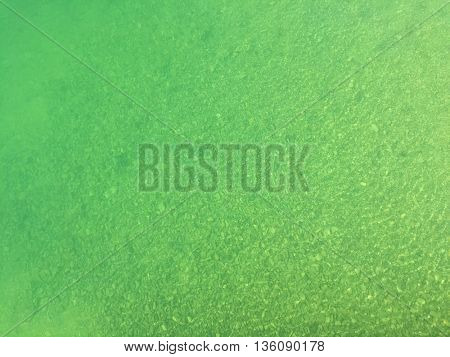 Blue green shade of fresh lake water above small stone pebble underwater with windy ripple texture during summer