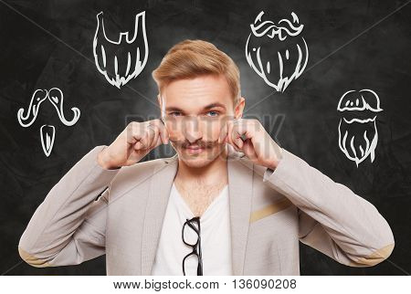 Man choose facial hair style, beard or mustache. Barber shop haircuts choice. Male fashion, various beard styles drawings at blackboard. Stylish young guy think of changing hairstyle. Man portrait
