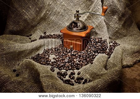 still life with old coffee grinder and beans on burlap