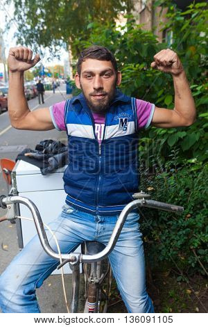 ZAGREB, CROATIA - OCTOBER 15, 2013: Young Roma man sitting on a bicycle and posing for camera at garbage dump.