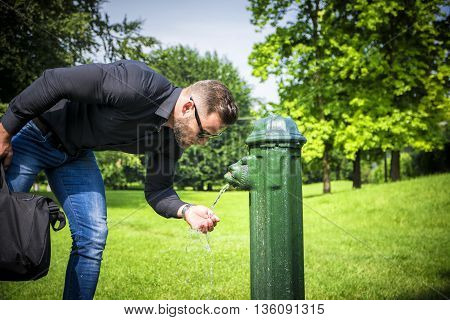 Side view of busy man in sunglasses with suitcase drinking water from fountain in summer park