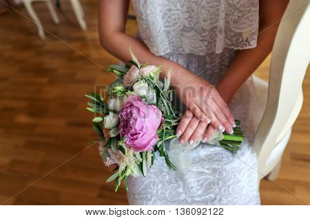 Bride sitting, bouquet of peonies on lap the bride