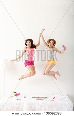 Joyful young women are springing on bed with joy. They are looking at camera and laughing