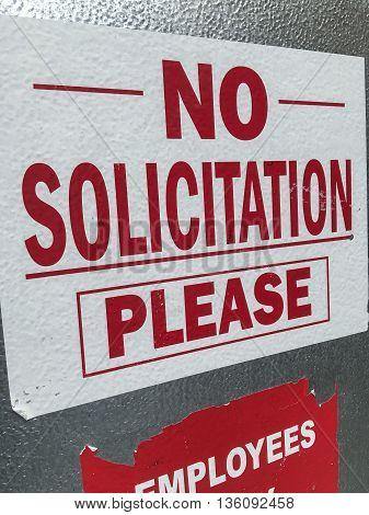 A no solicitation sign stug to a door on a freezer.