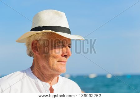 Senior man with hat portrait at the beach