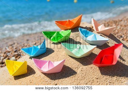 Paper boats in the sand at the beach