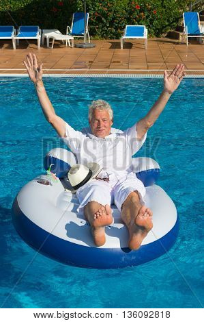 wealthy man cheering and relaxing in own swimming pool