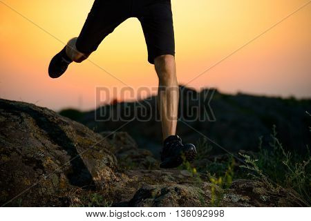 Close-up of Sportsman's Legs Running on the Rocky Mountain Trail at Night. Active Lifestyle Concept