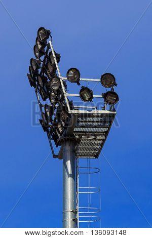 Stadium lights turned off against blue sky