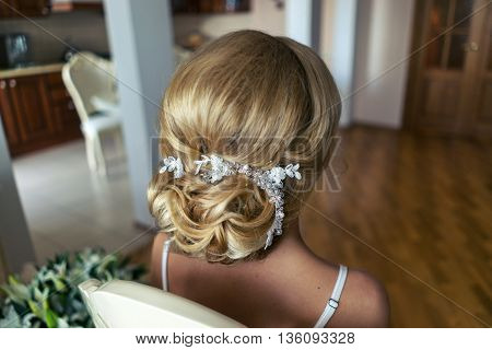 Portrait of attractive young woman with beautiful hairstyle and stylish hair accessory, rear view