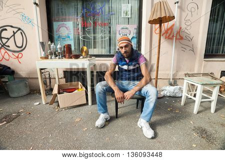 ZAGREB, CROATIA - OCTOBER 17, 2013: Young Roma man sitting at the chair at street garbage dump.
