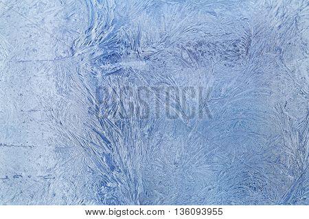 Frosty blue patterns on glass. Horizontal orientation of a shot light strip at the left