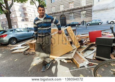 ZAGREB, CROATIA - OCTOBER 17, 2013: Young Roma man at street garbage dump.