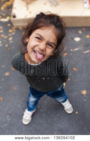 ZAGREB, CROATIA - OCTOBER 14, 2013: Portrait of cute Roma girl  sticking out tongue for camera at garbage dump.
