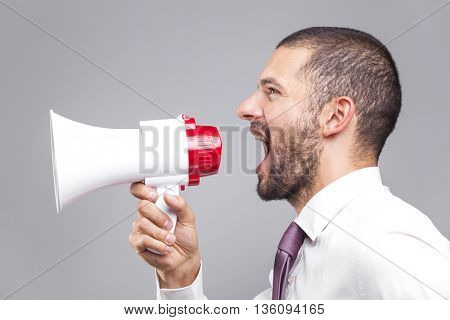 Young business man shouting by megaphone on grey background