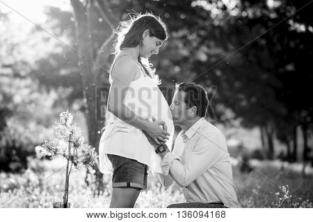 young happy beautiful couple in love walking together on grass and trees park landscape on sunset in summer with man kissing pregnant belly of his woman in family concept in black and white