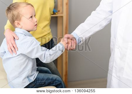 Well done. Happy little boy and paediatrician shaking hands after medical checkup